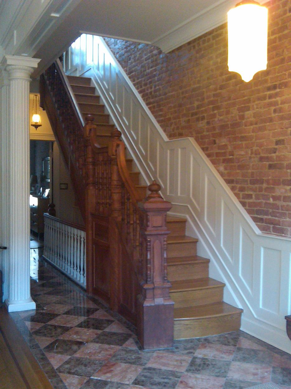 Parlor Entry: original mahogany stair railing up to living floor, exposed brick, vintage lighting.