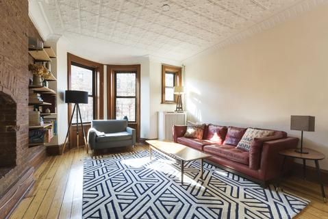 living room with 3 bay windows, decorative fireplace, original tin ceilings