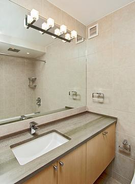 Floor to ceiling tiles.  Large mirror.  Granite counter.  Lighting and rain shower over large tub.