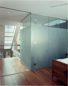 The master bath is enclosed by an elegant glass box, and topped by a large skylight