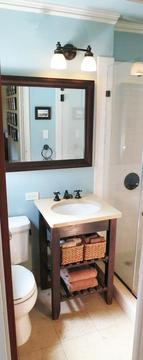 Open bathroom with glass shower doors and south facing window.