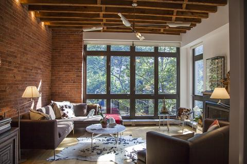 Southern-facing Living Room with gas FIREPLACE and floor to ceiling windows looks out on trees