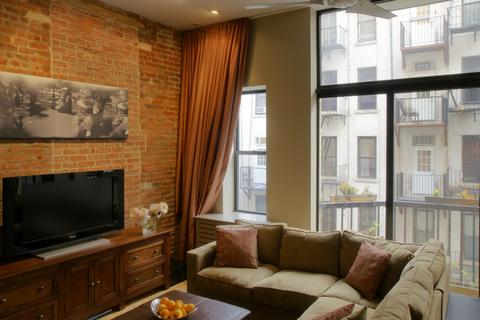 2nd Level Living Room with floor to ceiling windows and exposed brick wall