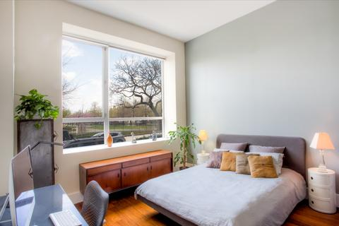 Oversized bedroom with large window looking out onto park.