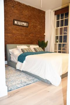 Exposed brick in large bedroom with great closet