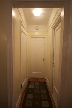 Hallway to bedroom, bathroom on right and linen closet on left