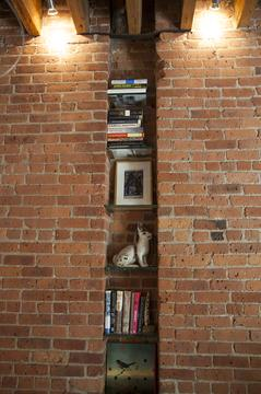 Tons of character and quality. Detail of a bookshelf in the brick wall