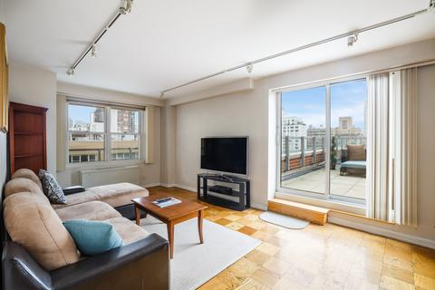 Large living room with plenty of windows and light! Easily convertible to legal extra bedroom.