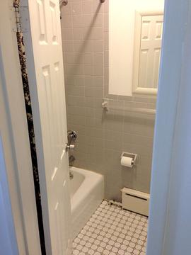 Bathroom tub/shower with floor to ceiling subway tiles.
