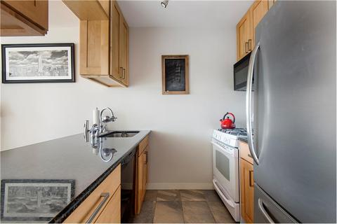 Gut-renovated kitchen with stone floors, granite counter
