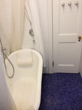 Recently renovated bath with claw foot tub and mosaic tile.