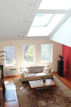 21'x17' living room has 10 ft ceiling, skylights, and wood burning stove