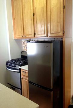 Renovated kitchen with stainless steel refrigerator and gas range.